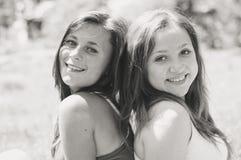 Zwei glückliche Freundinnen, die im grünen Sommerpark umarmen Lizenzfreie Stockbilder