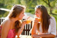 Zwei glückliche Freundinnen im Terrassekaffee u. -c$plaudern Stockfotografie