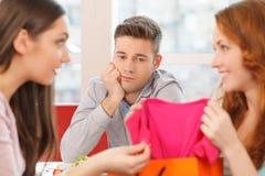 Zwei glückliche Freundinnen und ein Junge am Café stockfoto