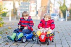 Zwei glückliche Freundjungen, die mit buntem Spielzeugauto, draußen spielen Stockfoto
