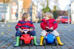 Zwei glückliche Freundjungen, die mit großem altem Spielzeugauto, draußen spielen Stockbild