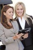 Zwei glückliche Geschäftsfrauen, die einen Tablette-Computer verwenden Lizenzfreies Stockfoto