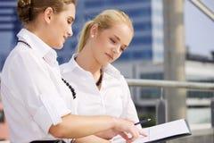Zwei glückliche Geschäftsfrauen mit Papierdiagramm Lizenzfreies Stockfoto