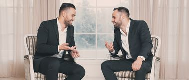 Zwei glückliche Geschäftsmänner, die bei der Sitzung über Hintergrund des Fensters sich besprechen lizenzfreie stockfotos