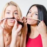 Zwei glückliche hübsche Freundinnen oder Schwestern, die mit dem Haar spielen Lizenzfreies Stockbild