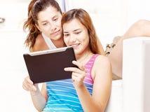Zwei glückliche Jugendlichen, die Berührungsflächencomputer verwenden Lizenzfreies Stockbild