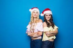 Zwei glückliche junge blonde und Brunettefrauenabnutzung in Sankt-Hut auf blauem Hintergrund, Weihnachts- und des neuen Jahressti Stockbilder