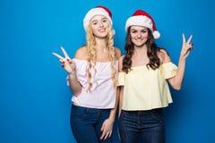Zwei glückliche junge blonde und Brunettefrauenabnutzung in Sankt-Hut mit Sieggeste auf blauem Hintergrund, Weihnachts- und des n Stockbild