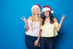 Zwei glückliche junge blonde und Brunettefrauenabnutzung in Sankt-Hut mit Sieggeste auf blauem Hintergrund, Weihnachts- und des n Lizenzfreie Stockfotos
