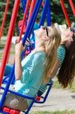 Zwei glückliche junge Frauen auf Schwingen Stockfotografie