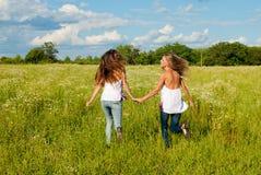 Zwei glückliche junge Frauen, die auf grünes Feld laufen Stockbild