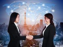 Zwei glückliche junge Geschäftsfrauen, die Hände rütteln Stockfoto