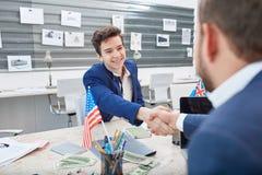 Zwei glückliche junge Männer rütteln Hände mit einander Innerhalb des Büros Lizenzfreie Stockfotografie