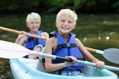 Zwei glückliche Jungen, die auf dem Fluss Kayak fahren Stockfotos