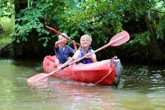 Zwei glückliche Jungen, die auf dem Fluss Kayak fahren Stockbilder