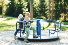Zwei glückliche Jungen, die auf Spielplatz in einem Park spielen Lizenzfreie Stockfotos