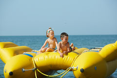 Zwei glückliche Kinder, die auf dem Boot am Sommertag spielen Stockfotografie