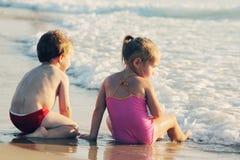 Zwei glückliche Kinder, die auf dem Strand spielen Stockfotos