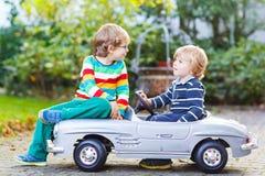 Zwei glückliche Kinder, die mit großem altem Spielzeugauto im Sommer spielen, arbeiten, ou im Garten Lizenzfreie Stockfotos