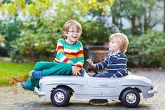 Zwei glückliche Kinder, die mit großem altem Spielzeugauto im Sommer spielen, arbeiten, ou im Garten Lizenzfreies Stockfoto