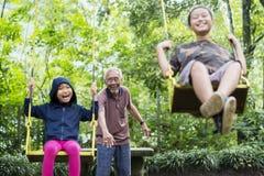 Zwei glückliche Kinder, die mit ihrem Großvater spielen Lizenzfreie Stockbilder