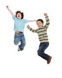 Zwei glückliche Kinder, die sofort springen Stockbilder