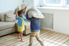 Zwei glückliche Kinder ist das Kämpfen Kissen lizenzfreie stockfotografie