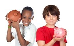 Zwei glückliche Kinder mit moneybox Sparungen Stockbilder