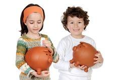 Zwei glückliche Kinder mit moneybox Sparungen Stockbild