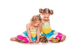 Zwei glückliche Kinder mit Osterhasen und Eiern. Fröhliche Ostern Lizenzfreie Stockfotos