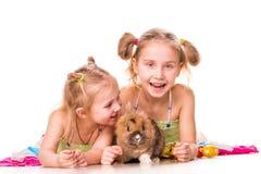 Zwei glückliche Kinder mit Osterhasen und Eiern. Fröhliche Ostern Stockbild