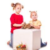 Zwei glückliche Kinder mit Osterhasen und Eiern. Fröhliche Ostern Stockfotos