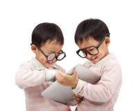 Zwei glückliche Kinder unter Verwendung des Notenauflagecomputers Stockfotografie