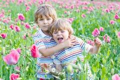 Zwei glückliche kleine blonde Kinder auf dem blühenden Mohnblumengebiet Lizenzfreie Stockbilder