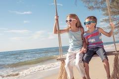 Zwei glückliche kleine Kinder, die auf dem Strand zur Tageszeit spielen Lizenzfreies Stockfoto