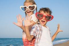 Zwei glückliche kleine Kinder, die auf dem Strand zur Tageszeit spielen Stockbild
