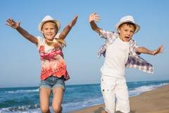 Zwei glückliche kleine Kinder, die auf dem Strand zur Tageszeit spielen Stockfoto