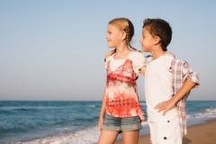 Zwei glückliche kleine Kinder, die auf dem Strand zur Tageszeit spielen Stockfotografie