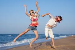 Zwei glückliche kleine Kinder, die auf dem Strand zur Tageszeit spielen Lizenzfreie Stockfotografie