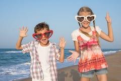 Zwei glückliche kleine Kinder, die auf dem Strand zur Tageszeit spielen Lizenzfreie Stockbilder