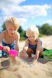 Zwei glückliche kleine Kinder, die im Sand am Strand spielen Stockbilder