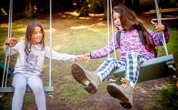 Zwei glückliche kleine Mädchen, die auf dem Schwingen schwingen Lizenzfreies Stockbild