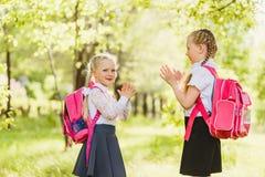 Zwei glückliche kleine Mädchen, die draußen Patty-Kuchen spielen stockbild