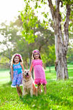 Zwei glückliche kleine Mädchen und ein goldener Apportierhund Stockbild