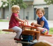 Zwei glückliche kleine Schwestern auf schaukelndem Brett Lizenzfreie Stockbilder