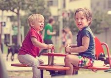 Zwei glückliche kleine Schwestern auf schaukelndem Brett Stockbilder