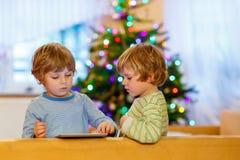 Zwei glückliche Kleinkinder, die mit Tabletten-PC spielen Lizenzfreie Stockfotos
