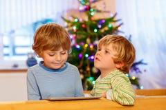 Zwei glückliche Kleinkinder, die mit Tabletten-PC spielen Stockfoto
