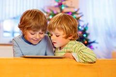 Zwei glückliche Kleinkinder, die mit Tabletten-PC spielen Lizenzfreie Stockbilder