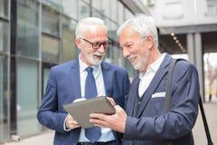 Zwei glückliche lächelnde ältere graue behaarte Geschäftsmänner, die an einer Tablette arbeiten stockfoto